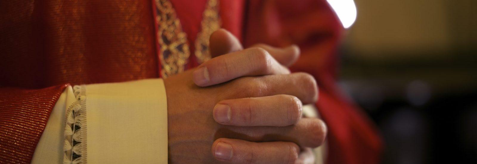 Priester handen gevouwen